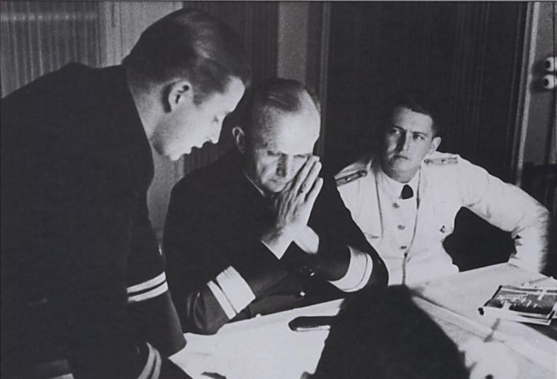 A young U-boat commander on a debriefing with Donitz, while his adjutant (in white...