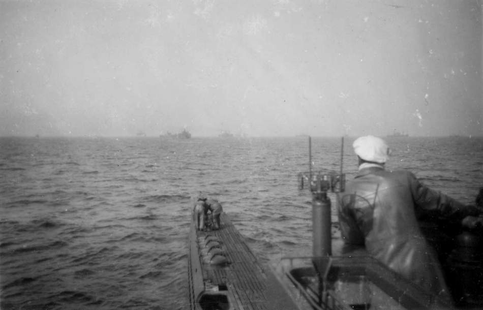 A U-boat stalking a convoy, which can be seen scattered ahead.
